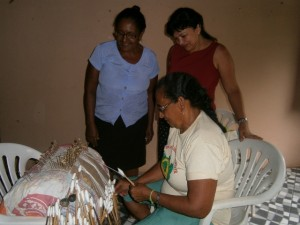 Donna Vicencia shows Rosalba how the women make crafts using local skills and techniques